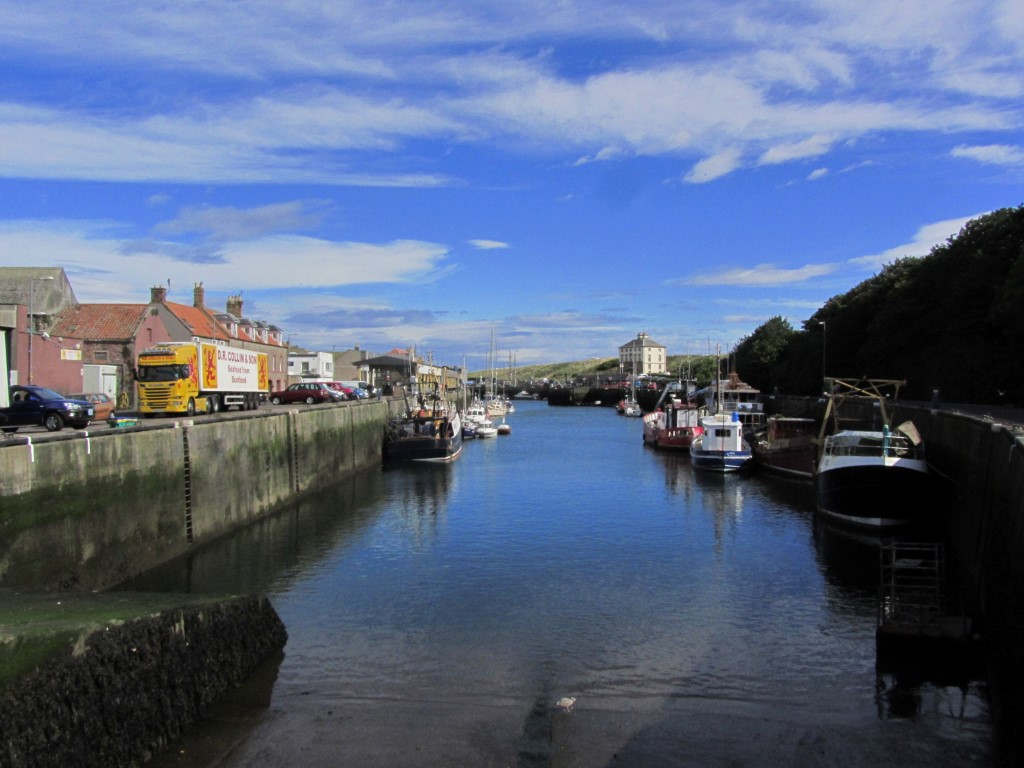 Eyemouth Harbour on a still fine summer's morning. In the distance is Gunsgreen House famed for its smuggling history.