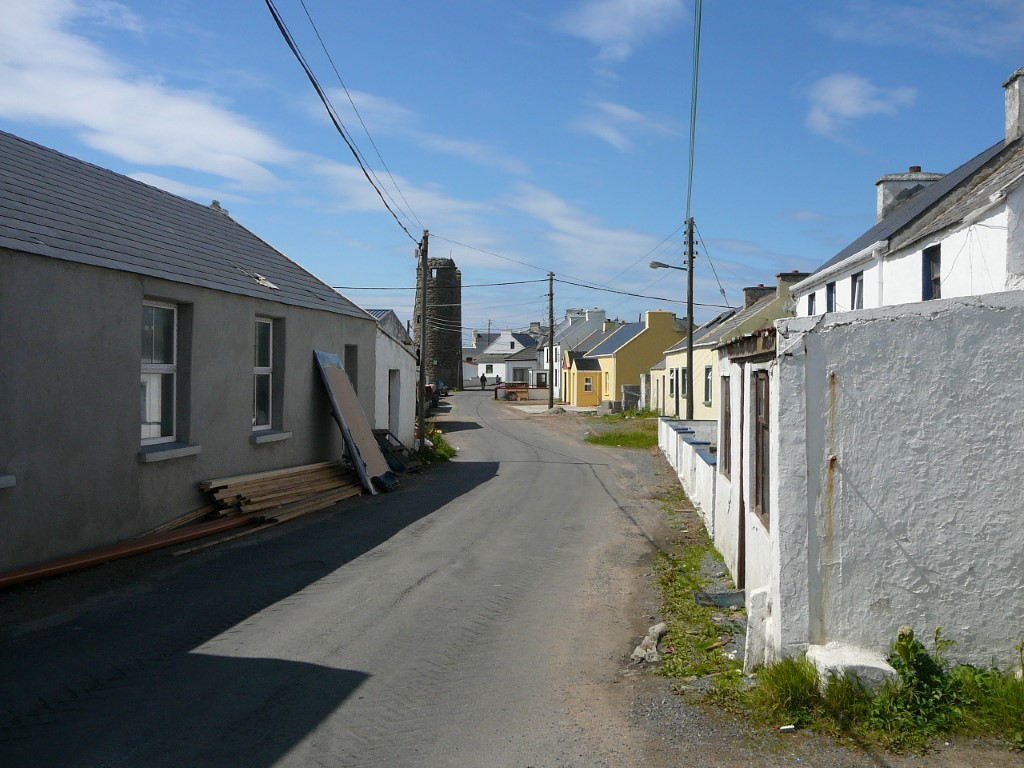 the main village street on tory Island dominated by the round tower of the former