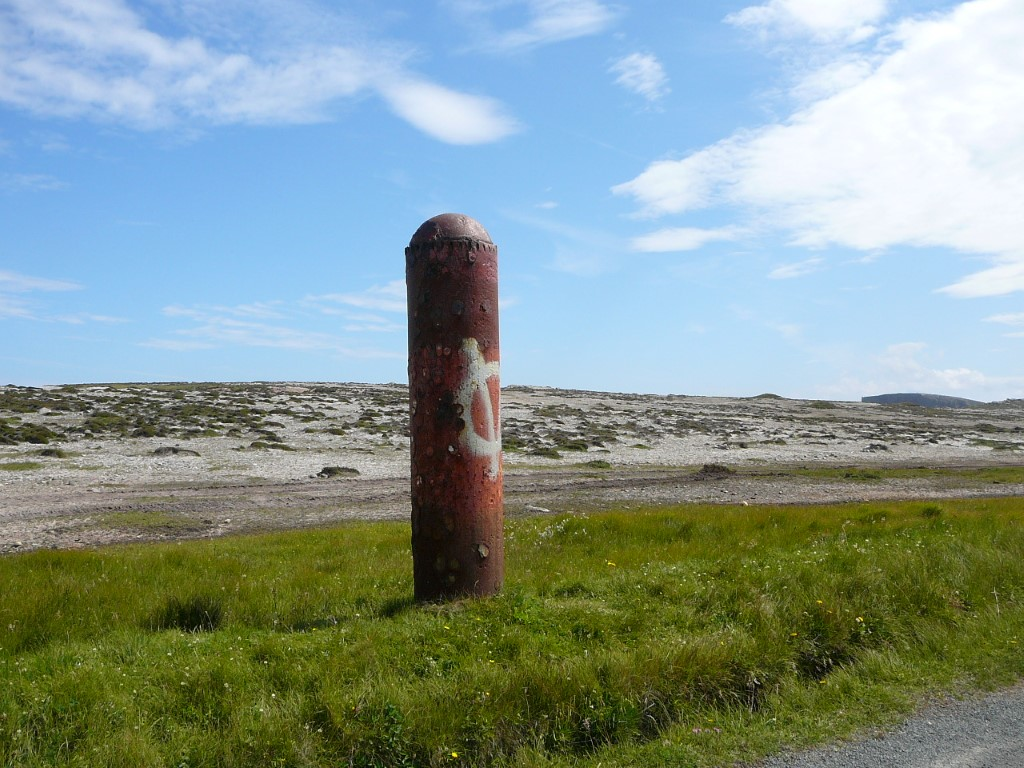 Now who left this here! A rusting torpedo upended by the island road.