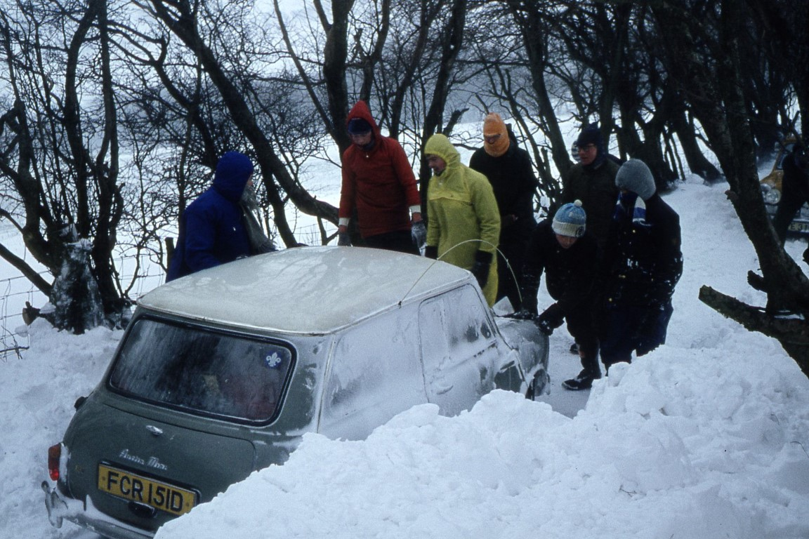 All hands to the pump. Trying to push a car up a slippery slope.